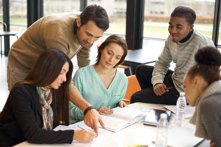 テーブルで一緒に彼らの研究をしている若い学生の多民族のグループ。その学校の割り当てとの連携で混血の人々。