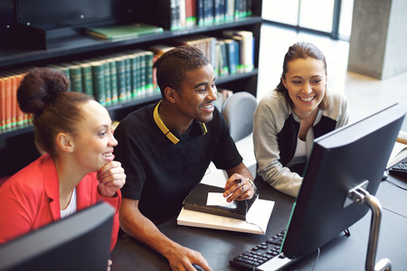 diverse students: Diverse group of students using computer for finding information for their academic project. Happy young people sitting at table with books and computer taking notes for their study. Stock Photo