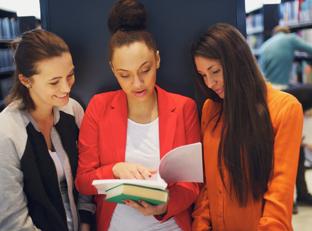 reference book: Three young female students standing in the library and looking at a book together. University students reading reference books for their studies.