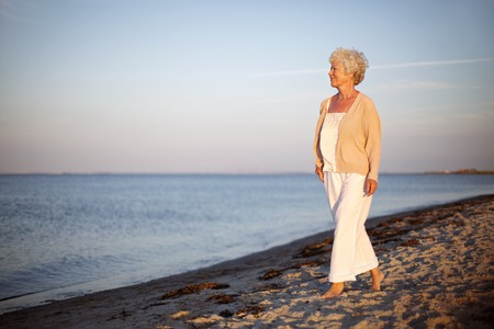 Portrait of a mature woman walking on the beach looking at the sea. Relaxed old lady strolling on the beach with lots of copyspace. Stock Photo