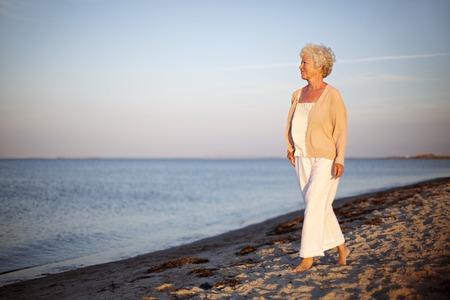 Portret van een volwassen vrouw lopen op het strand kijken naar de zee. Ontspannen oude dame een wandeling op het strand met veel copyspace.