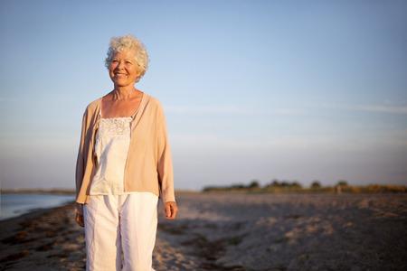 카메라를 찾고 해변에서 서 행복 성숙한 여자의 초상화. 늙은 아가씨 혼자 서 해변에 웃 고. 편안한 수석 백인 여자가 야외에서