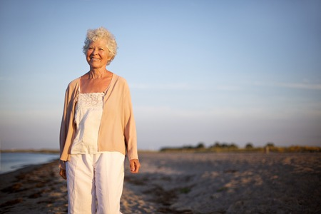 Portrait of happy mature woman standing at the beach looking at camera. Smiling old lady standing alone on the beach. Relaxed senior caucasian woman outdoors photo