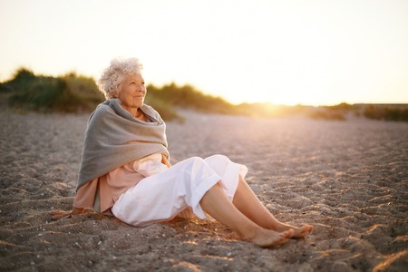 Image of relaxed elderly woman sitting on the beach looking at a view. Senior woman wearing shawl sitting on beach.