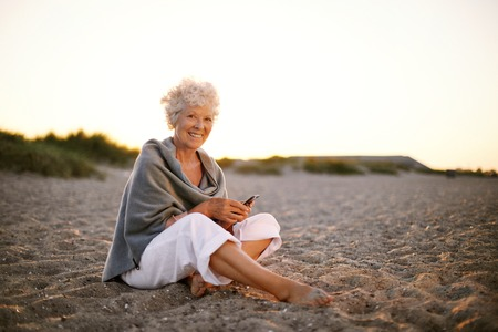 Gelukkig gepensioneerde vrouw zit ontspannen op het strand met een mobiele telefoon in de hand. Senior blanke vrouw met een mobiele telefoon op het strand buiten Stockfoto