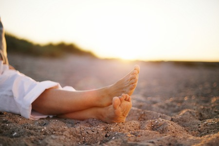 Closeup image of legs of senior woman sitting relaxed on sandy beach.