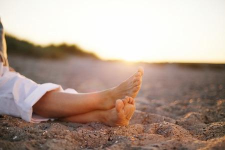 piernas mujer: Imagen de detalle de las piernas de la mujer mayor que se sienta relajado en la playa de arena. Foto de archivo