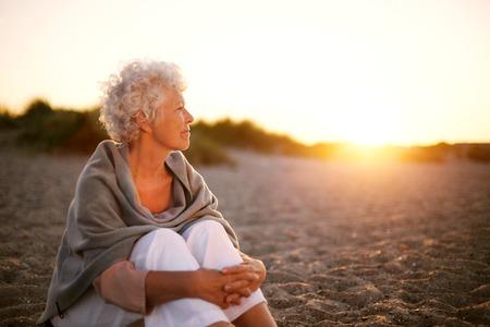 Oude vrouw zittend op het strand weg te kijken op copyspace. Senior vrouw zitten buiten Stockfoto