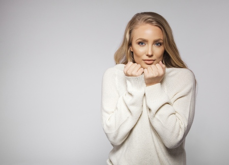 Portrait of beautiful young blonde wearing sweater feeling cold. Cute young female fashion model posing on grey background with copyspace. photo