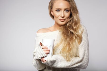 oversized: Portrait of attractive young wearing sweater holding a hot cup of coffee. Caucasian female fashion model on grey background with copyspace.
