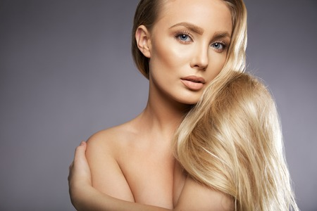 Close up portrait of attractive young woman topless looking at camera. Young caucasian female model with long blond hair against grey background, with lots of copy space. photo