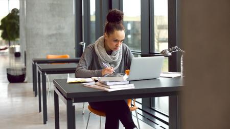 정보를 찾기위한 책 및 노트북 테이블에 앉아 젊은 아프리카 계 미국인 여자. 도서관에서 그녀의 연구를 위해 노트북과 책에서 메모를 복용하는 젊은