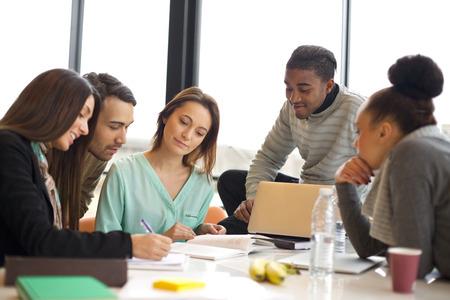 Různorodá skupina mladých studentů pracují společně na školní úkoly. Multietnické lidé studují pohromadě u stolu.