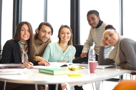 working on school project: Portrait of a group of positive university students sitting at table in library. Mixed race people studying together in library. Stock Photo
