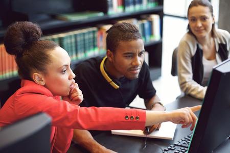 Malá skupina studentů vysokých škol, kteří pracují na počítači v knihovně. Mladí lidé vyhledávání informací o jejich přidělení vysoké školy.