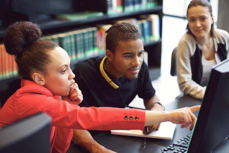 highschool student: Small group of university students working on computer in a library. Young people finding information for their college assignment.