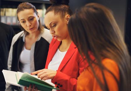 reference book: Tres j�venes mujeres estudiantes que estudian juntos para sus ex�menes. Las mujeres j�venes la lectura de un libro de referencia para obtener informaci�n. Foto de archivo