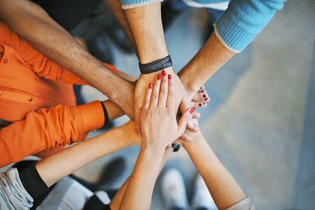 手のスタックのクローズ アップ。若い大学学生の団結とチームワークを象徴する互いの上に手を入れてします。