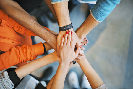 Nahaufnahme von Stapel von Händen. Junge Studenten ihre Hände auf der jeweils anderen symbolisiert Einheit und Teamwork.