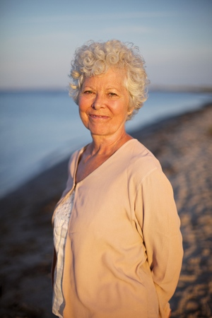 Portrait of beautiful old woman standing alone at the beach. Senior caucasian lady relaxing outdoors photo