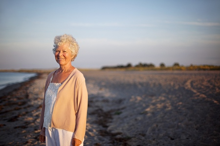 Portrait of relaxed elderly woman standing at the beach. Happy old lady standing alone on the beach with lots of copyspace. Relaxed senior caucasian woman outdoors smiling at camera photo