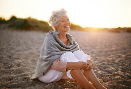Gelukkig gepensioneerde vrouw draagt sjaal zit ontspannen op het zand op het strand. Senior blanke vrouw zittend op het strand buiten Stockfoto