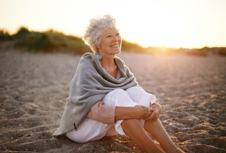 Happy retired woman wearing shawl sitting relaxed on sand at the beach. Senior caucasian woman sitting on the beach outdoors Stock Photo