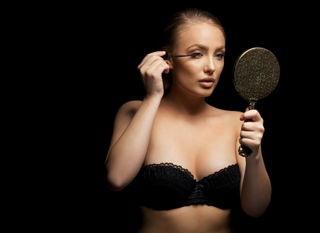 black bra: Beautiful young woman wearing black bra putting some mascara onto her eyelashes with make up brush. Sexy caucasian female model with mirror against black background. Stock Photo