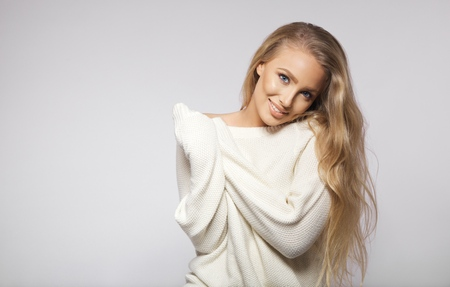 oversized: Stunning young female fashion model with long hair posing in oversized sweater. Young blond woman posing on grey background