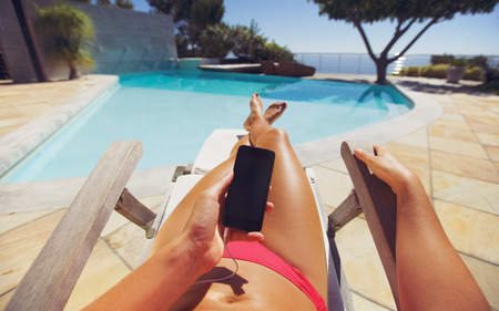 point of view: Tanned woman using smart phone by the poolside. Caucasian female model sunbathing on a deckchair and mobile phone. Stock Photo