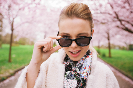 winking: Close up image of cute young woman winking at camera. Naughty female model at spring park wearing sunglasses. Stock Photo