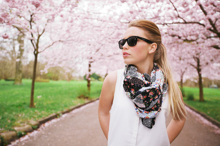 Attractive young woman posing at the spring blossom garden. Pretty caucasian female model standing outdoors at a park wearing sunglasses and scarf looking away.