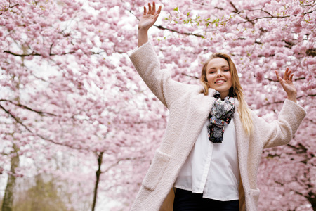 Low angle view of young woman at spring blossom park with her arms up looking at camera smiling.