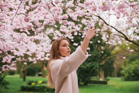 Young caucasian woman picturing blossom flowers with her mobile phone. Attractive woman photographing flowers at the spring garden - Outdoors photo