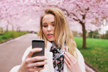 Attractive woman photographing herself at the spring garden. Beautiful young female model taking self portrait with her mobile phone. photo