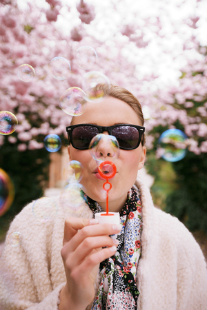 Cute young female wearing sunglasses blowing bubbles at spring park. Beautiful caucasian woman blowing soap bubbles. photo