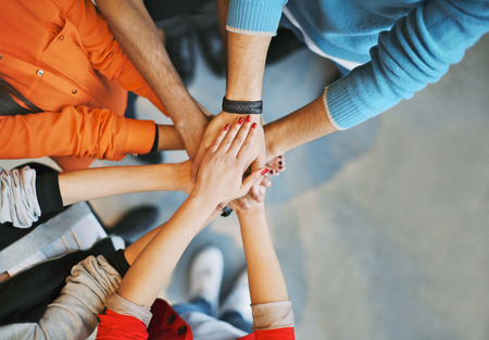 support group: Top view image of group of young people putting their hands together. Friends with stack of hands showing unity.