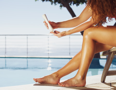 Woman sitting on deck chair by the swimming pool applying sun cream onto her legs. Female model sunbathing at the poolside.