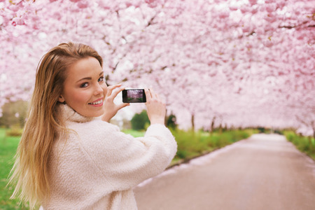 Young woman using her smartphone to capture images of the path and cherry blossoms tree at park, Young female looking over her shoulder while taking pictures with her mobile phone at spring blossom garden. photo