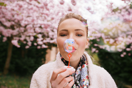 Portrait of beautiful young woman blowing bubbles at park. Pretty female model with bubble wand at spring blossom garden. photo