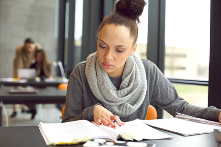 exams: Female student reading a book for finding information. Young african american woman sitting at table doing assignments in university library. Stock Photo