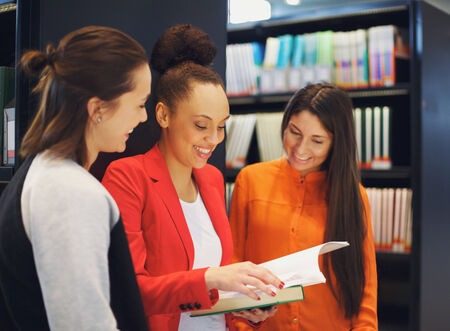 reference book: Diverse group of college students in library reading a book together. Female students looking for information in reference books for their studies. Stock Photo
