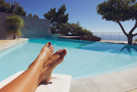 feet relaxing: Bare feet of young lady lying on deck chair sunbathing by the swimming pool.