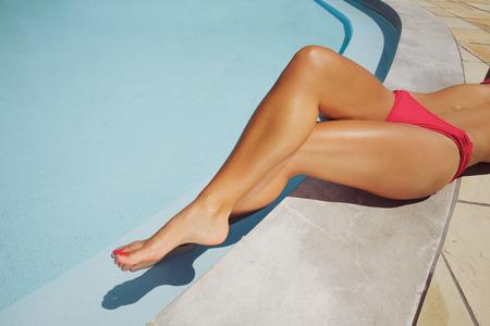 Bovenaanzicht van een mooie vrouwelijke fashion model ontspannen op de rand van een zwembad. Gekruiste benen van de jonge vrouw rust bij het zwembad. Stockfoto