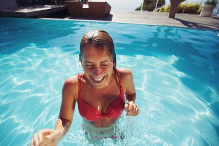 wet bikini: Young woman enjoying herself in a pool. Cheerful caucasian female wearing bikini in swimming pool. Stock Photo