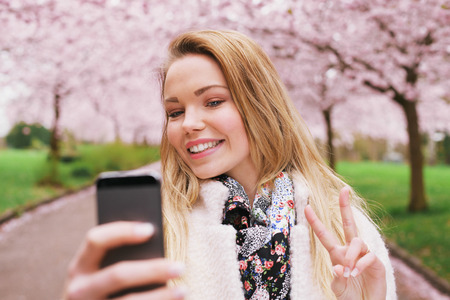 Pretty young female model gesturing peace sign while taking her picture with cell phone. Beautiful caucasian young woman taking self portrait while at spring blossom park. photo
