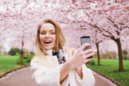 Happy young woman photographing herself using her mobile phone. Caucasian female talking selfie with her smart phone at park. photo