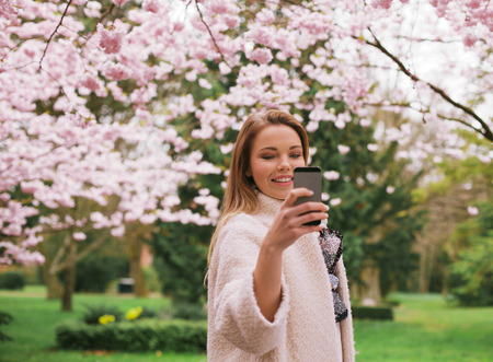 Beautiful young female taking pictures of with smartphone at spring blossom park. Caucasian female shooting at park with her mobile phone. photo