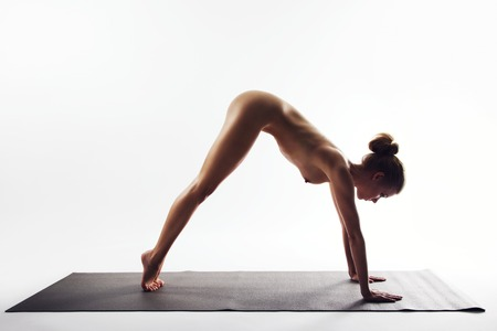 Naked young women performing stretching exercise on white background. Yoga forward bend pose demonstrated by nude female model. photo