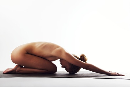 Nude young woman stretching and doing meditation on exercise mat. Caucasian female practicing yoga over white background. photo